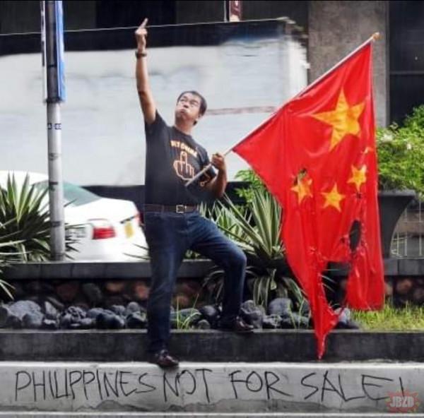 Filipiński dziennikarz Waldek Carbonell pali Chińską flagę i pokazuje środkowy palec przed budynkiem ambasady Chin.